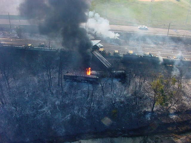 Overhead shot of the train derailment, fire started between two rail cars, charring the surrounding area.