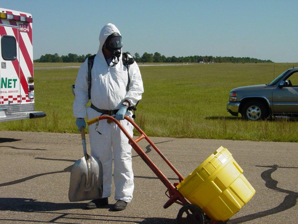 An officer in a hazmat suit, pulling a container for dangerous materials on a dolly.