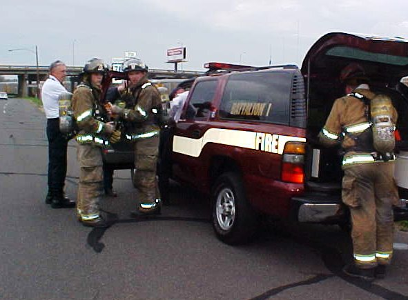 Fire fighters in full gear standing around their red SUV, waiting for instructions.