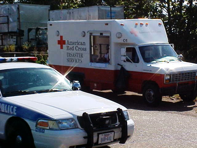 Red Cross Disaster services van sits behind a police cruiser.