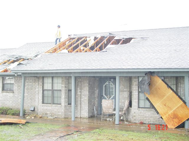 Plywood pushed up against the house, roof damage from the storm.