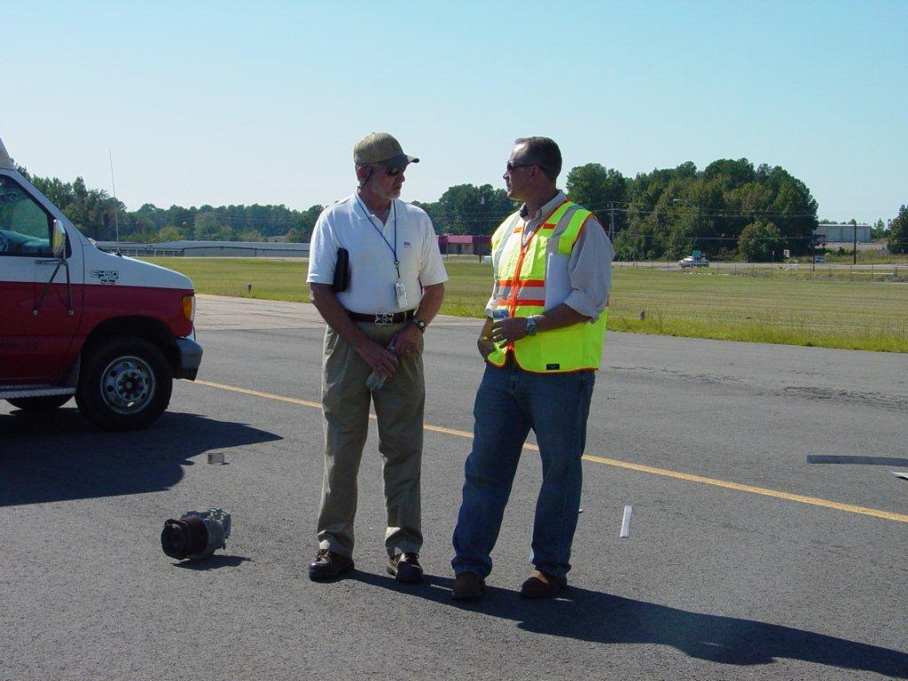 Two officers standing on the airport runway.