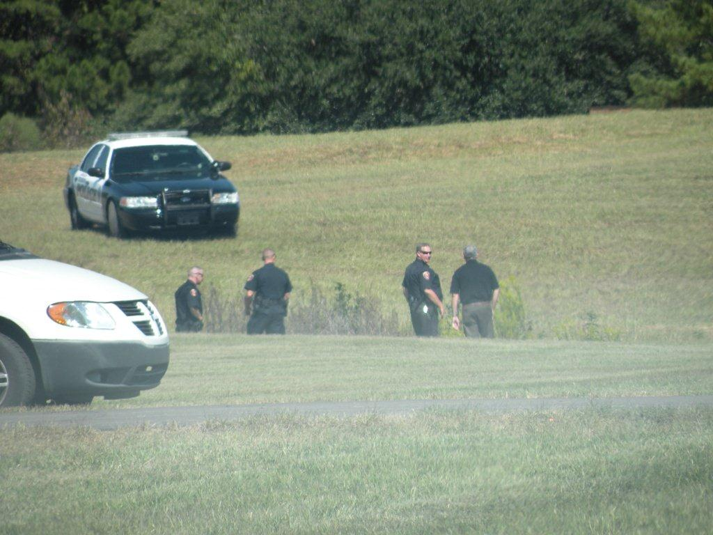 Police officers waiting in a field.