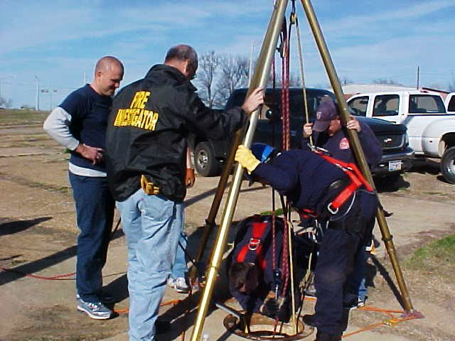 Fire fighters standing around the manhole rigging, double checking safety gear.