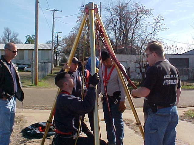 Fire fighters strapping into the rigging to get them down the manhole.