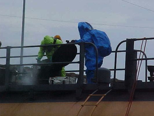 Fire fighters learning how to diffuse a dangerous rail car, while wearing HazMat suits.