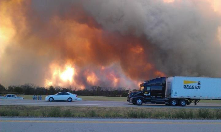 Vehicles stopped on the highway, large smoke clouds rising in the distance.